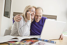 Frau, die mit ihrem Mann auf einem Handy vor einem Laptop sitzt.