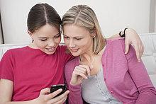 Frau und Tochter beim Lesen einer SMS auf dem Handy