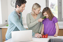 Familienkochen mit dem Rezept auf dem Laptop
