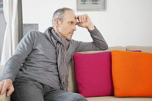 Ein Mann, der auf einer Couch sitzt und nachdenkt.