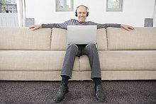 Mann mit einem Laptop und Musik hören