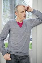 Ein Mann, der vor einem Fenster steht und nachdenkt.