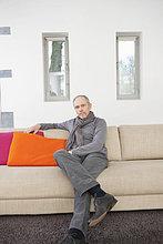 Porträt eines Mannes, der auf einer Couch sitzt