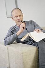 Porträt eines Mannes, der ein Buch hält und lächelt