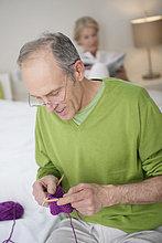Mann strickt mit einer Frau im Hintergrund