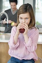 Mädchen trinkt Saft, ihr Vater steht hinter ihr.