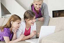 Zwei Mädchen, die einen Laptop auf einer Couch benutzen, während ihre Großmutter neben ihnen steht.