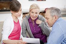 Mädchen beim Lesen eines Dokuments mit ihren Großeltern