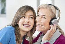Frau mit ihrer Enkelin beim Hören von Kopfhörern