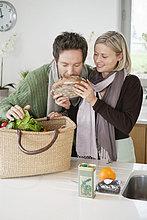 Mann riecht einen Laib Brot, seine Frau steht neben ihm.