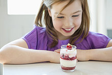Mädchen sieht sich ein Glas Eis an.