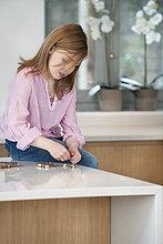 Mädchen sitzend auf einem Küchentisch