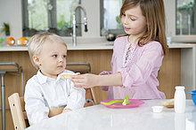 Mädchen füttert ihren Bruder