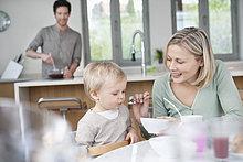 Frau füttert ihren Sohn mit Frühstück