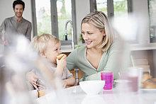 Frau beim Frühstücken mit ihrem Sohn