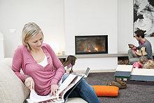 Frau beim Lesen einer Zeitschrift mit ihrer Familie im Wohnzimmer
