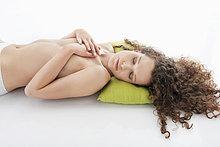 Frau, die ihre Brüste bedeckt und schläft.