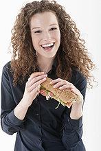 Eine Frau hält ein Sandwich und lacht.