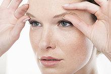 Nahaufnahme einer Frau beim Reiben der Augenbrauen