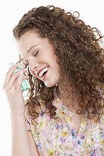 Nahaufnahme einer Frau, die eine Flasche Aromatherapieöl hält.