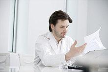 Männlicher Arzt bei der Untersuchung eines medizinischen Gutachtens