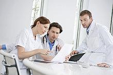Drei Ärzte bei der Untersuchung eines medizinischen Gutachtens