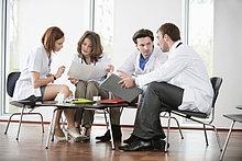 Ärzte, die auf Stühlen sitzen und medizinische Berichte besprechen