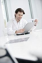 Ein männlicher Arzt, der einen medizinischen Bericht untersucht und lächelt.