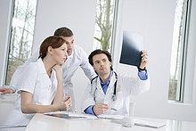 Drei Ärzte untersuchen einen Röntgenbericht