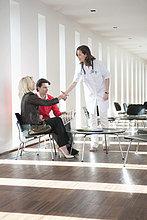 Ärztin, die einer Frau die Hand schüttelt.