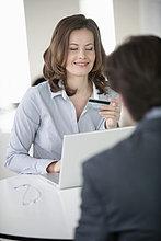 Geschäftsfrau, die einem Geschäftsmann eine Kreditkarte zeigt