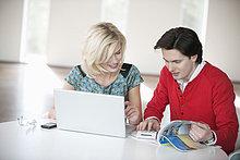 Paar mit einem Laptop und einem Taschenrechner