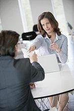 Geschäftsfrau, die einem Berater eine Rechnung vorlegt