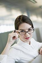 Porträt einer Geschäftsfrau, die über die Brille schaut und lächelt