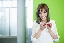 Geschäftsfrau hält eine Schale mit Kirschtomaten in der Hand