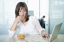 Geschäftsfrau isst Pasta und benutzt einen Laptop