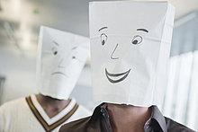 Zwei Geschäftsleute, die Papiertüten mit fröhlichen und traurigen Gesichtern tragen.