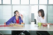Geschäftsfrau schaut einen Geschäftsmann an, der Kopfhörer hört und Blasen bläst.