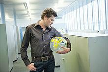 Geschäftsmann, der einen Globus hält und in einem Büro denkt.