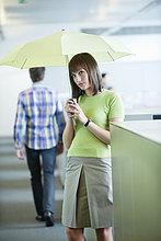 Geschäftsfrau mit Schirm im Büro