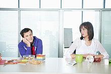 Geschäftsmann und Geschäftsfrau sitzen zusammen mit dem Essen auf dem Tisch