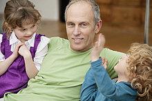 Mann sitzend mit seinen Enkeln