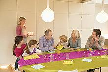 Familie bei einer Geburtstagsfeier mit einer Frau mit Kuchen im Hintergrund