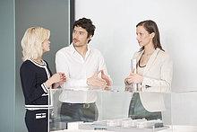 Mann mit zwei Frauen in der Nähe eines Architekturmodells