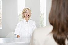 Krankenschwester schaut eine Frau an und lächelt.