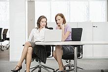 Zwei Geschäftsfrauen, die in einem Büro arbeiten.