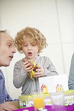 Junge öffnet sein Geburtstagsgeschenk mit seinem Großvater neben ihm
