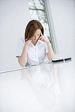 Eine Ärztin sitzt in einem Büro und sieht verärgert aus.