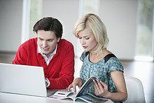 Mann mit einem Laptop und einer Frau, die eine Zeitschrift liest.
