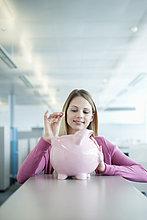 Geschäftsfrau beim Einwerfen einer Münze in ein Sparschwein